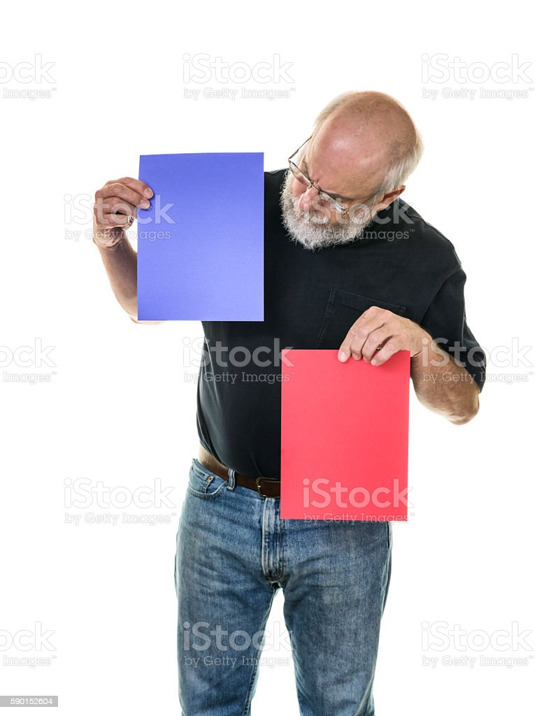 Political Election Senior Man Voter Comparing Blue and Red Ballots stock photo