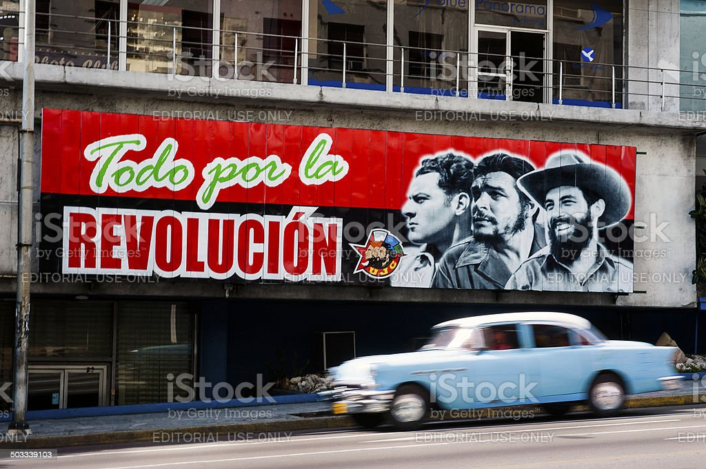 Political propaganda billboard in Havana with vintage car stock photo