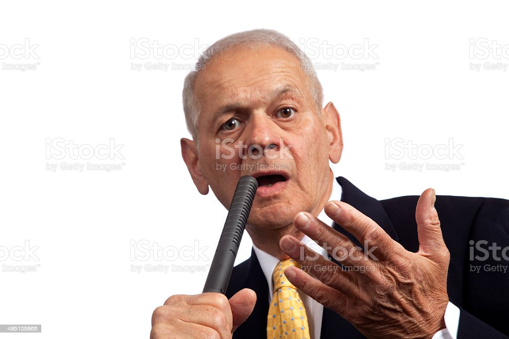 Politician holding microphone with a persuasive look facing camera stock photo