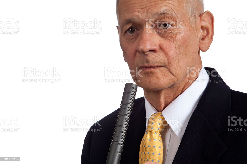 Politician holding microphone with worried look, facing camera stock photo