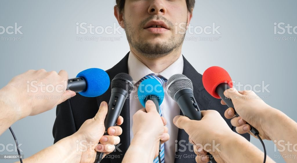 Politician is talking ang giving interview to reporters. Many microphones recording him in front. stock photo