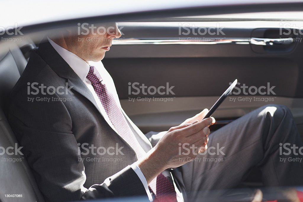 Politician reading in backseat of car stock photo