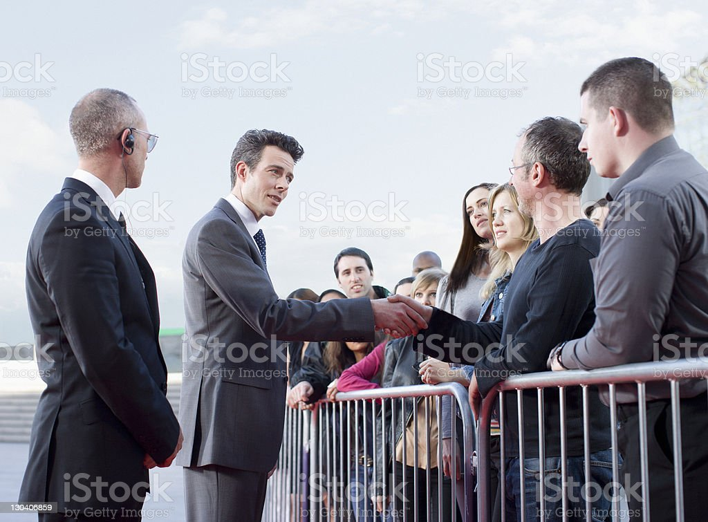 Politician shaking hands with people behind barrier stock photo