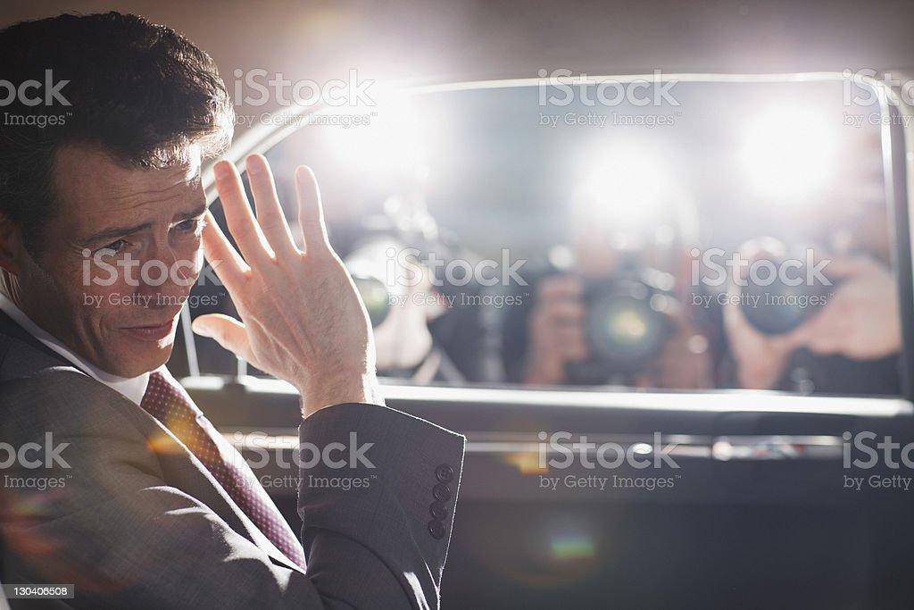Politician shielding himself from paparazzi royalty-free stock photo