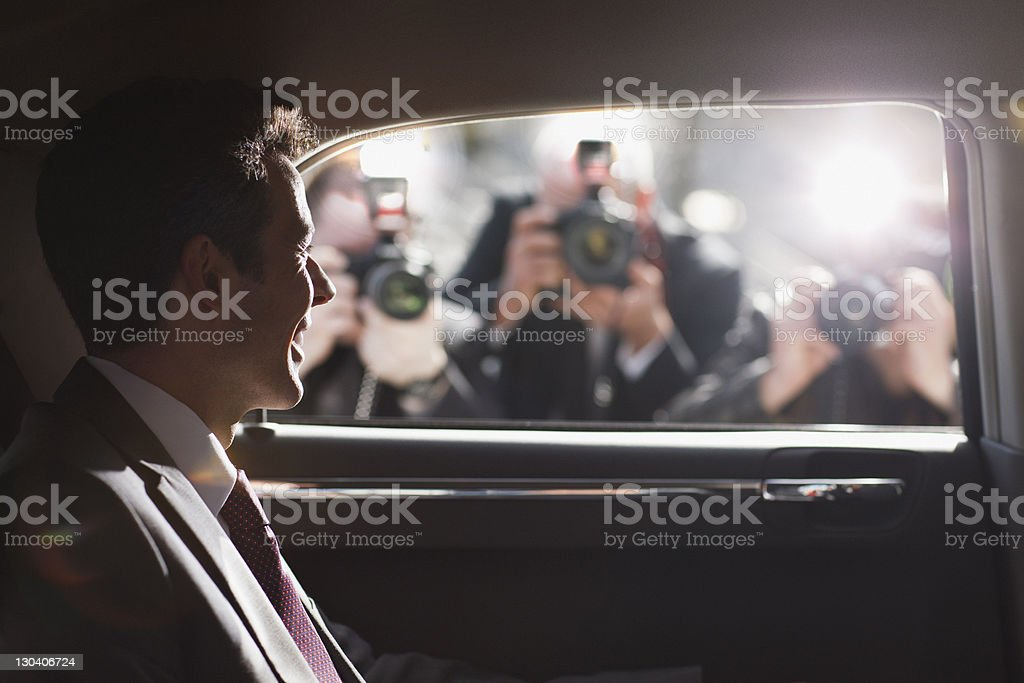 Politician smiling for paparazzi in backseat of car stock photo