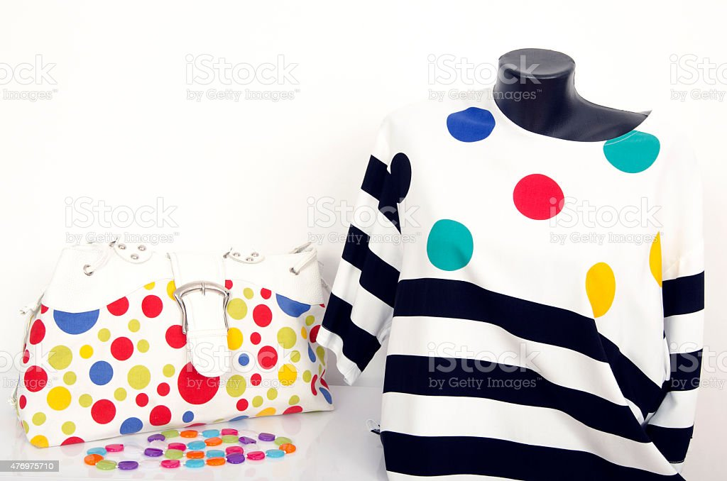 Polka dots and stripes blouse on mannequin with matching accessories. stock photo