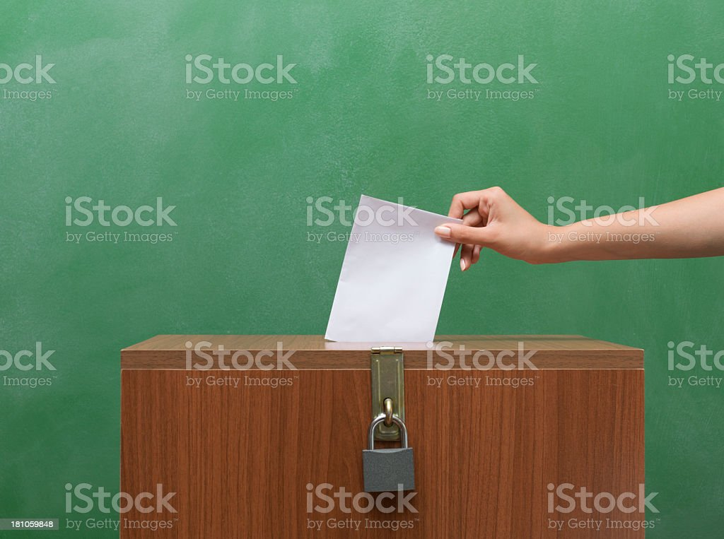 Poll Envelope In Human Hand Inserting To The Ballot Box stock photo