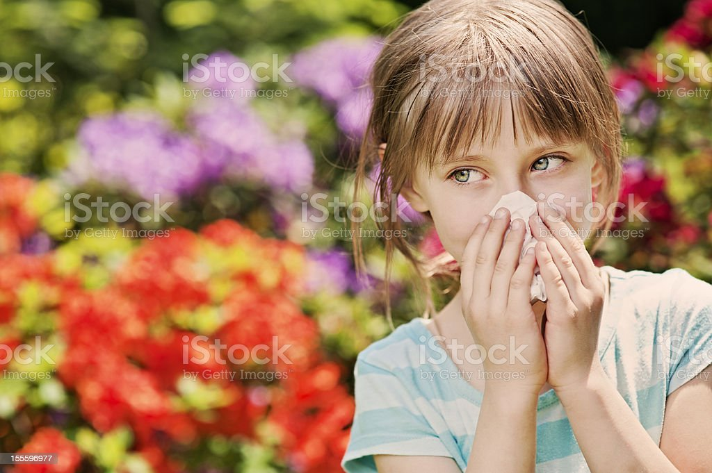 Little girl cleaning nose outdoors near flowers.