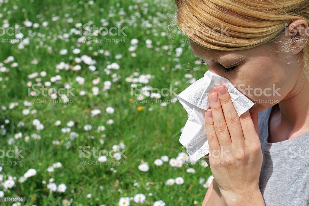 Pollen allergy, Springtime. Woman sneezing in a tissue stock photo