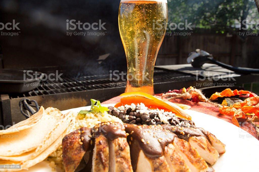Pollo Con Molé With Beans, Rice, Tortillas And A Beer stock photo
