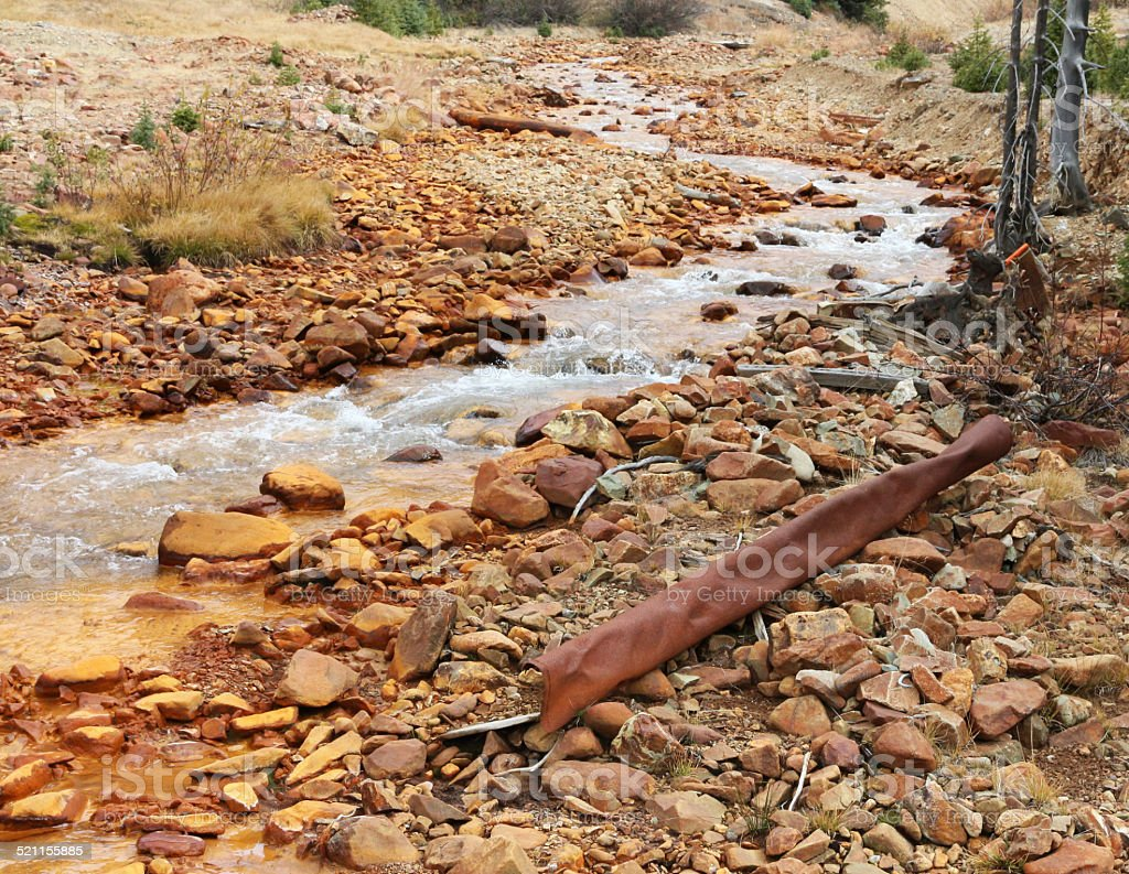 Polluted stream and rusted metal in Colorado stock photo