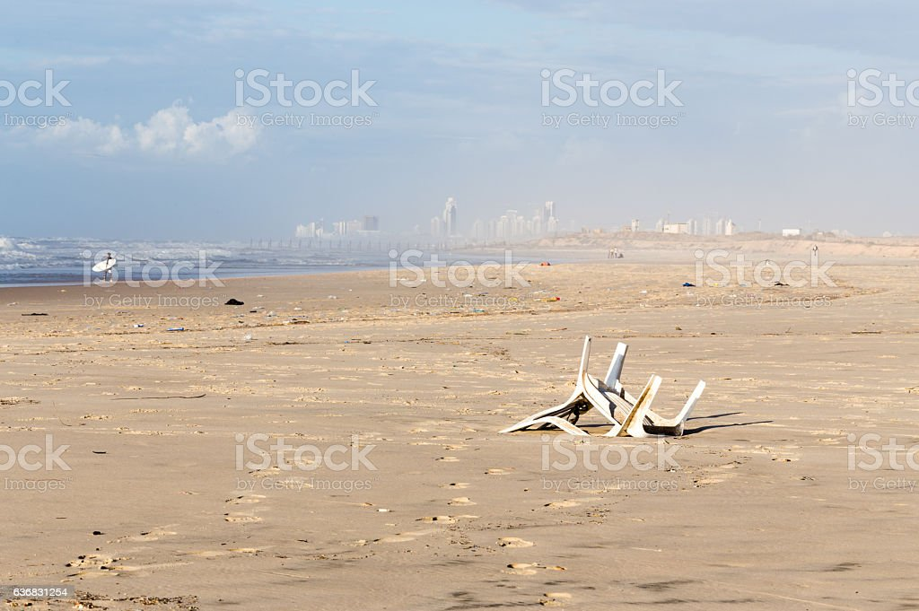 Pollution beach sea shore garbage plastic chair city view. stock photo