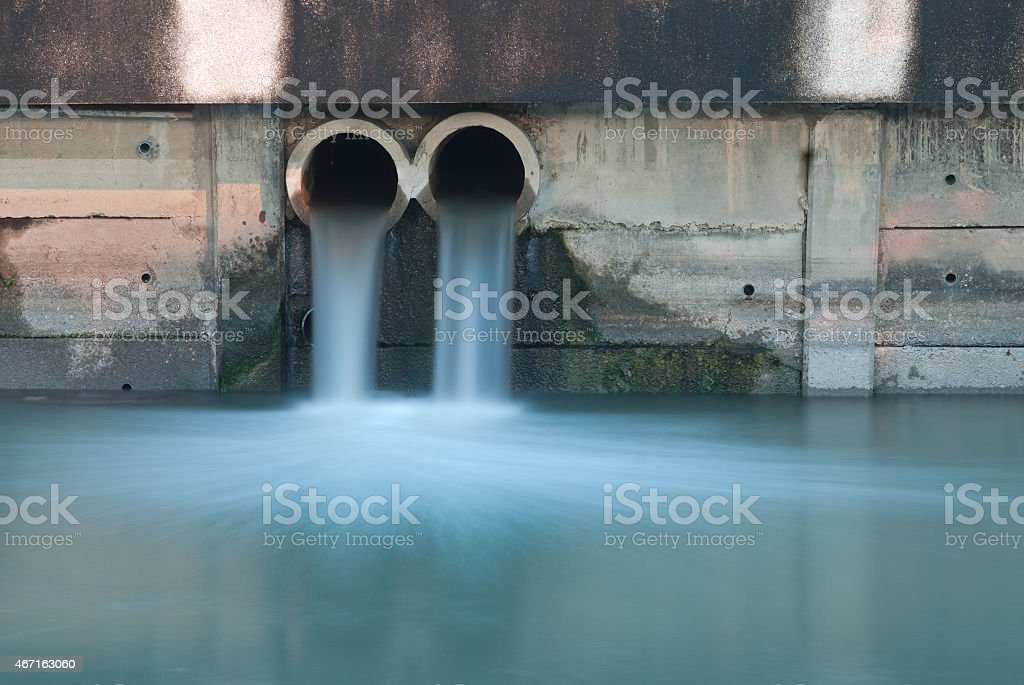 Pollution drain flowing stream to a river stock photo