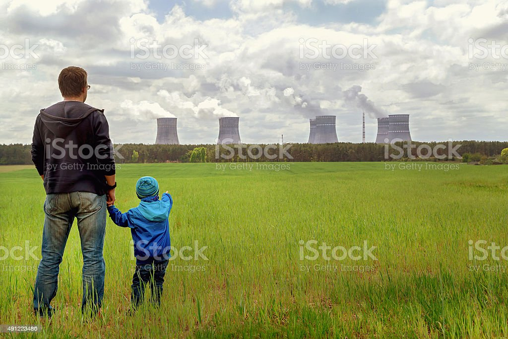 Pollution. Environmental problem. Father, son looking on emissions of plant. stock photo