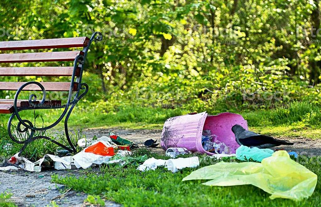 Pollution. Environmental problem. Garbage (rubbish) near bench in the park. stock photo