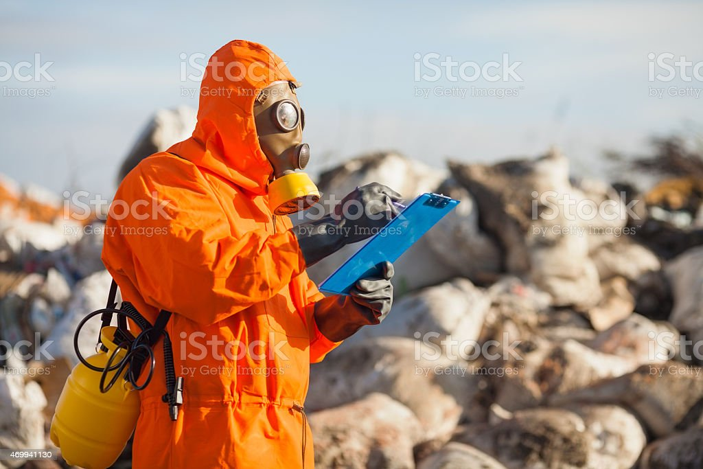 Pollution examiner in orange suit monitoring pollution stock photo