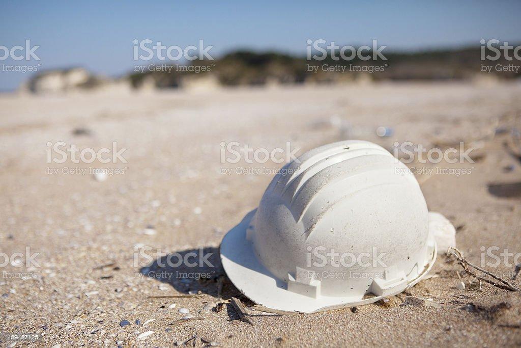 Pollution - Plastic Hard Hat on Beach stock photo