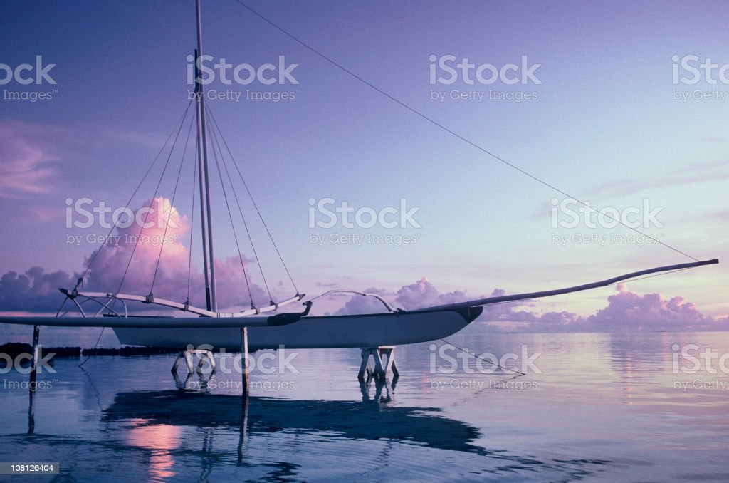 Polynesian Catamaran in Lagoon Water at Sunset royalty-free stock photo