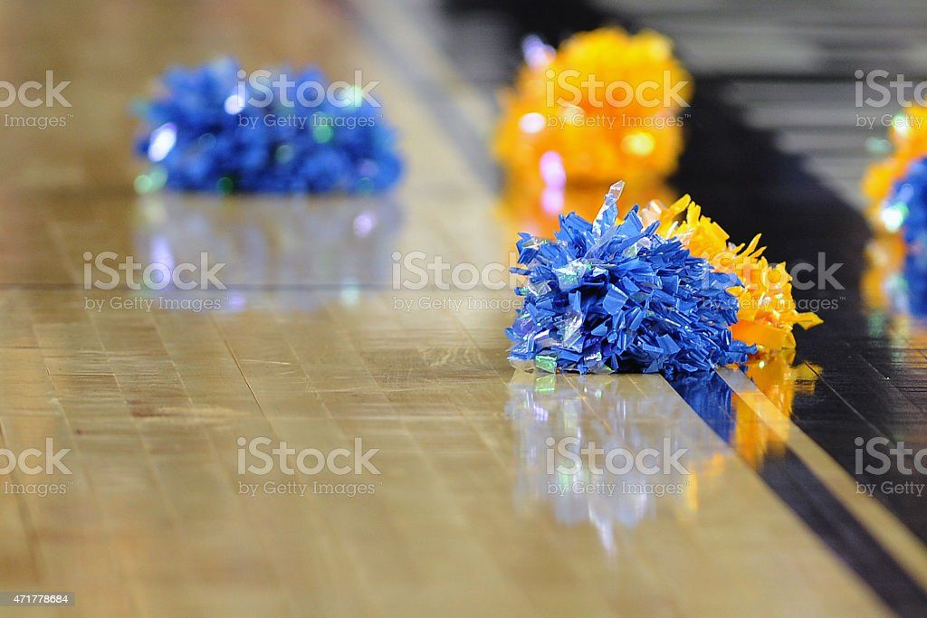 Pom poms on a collegiate basketball court. stock photo