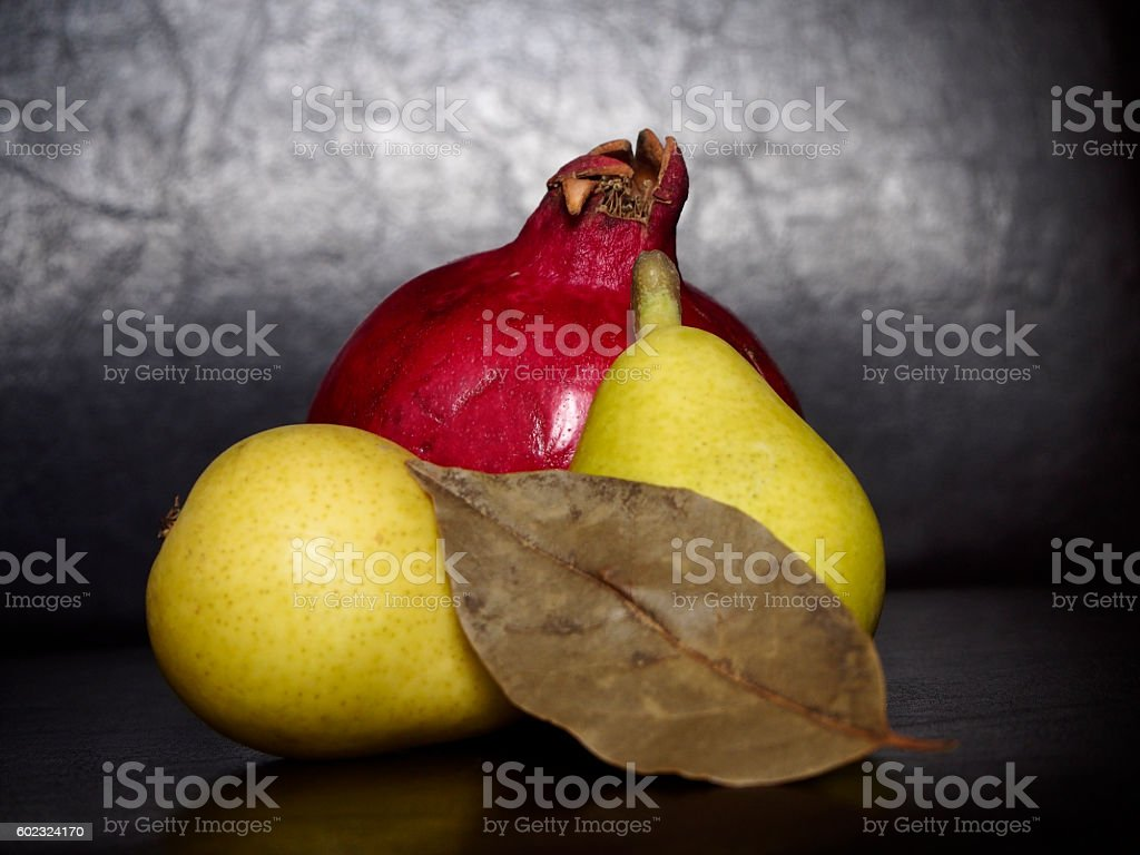 Pomegranate and pears on black background stock photo