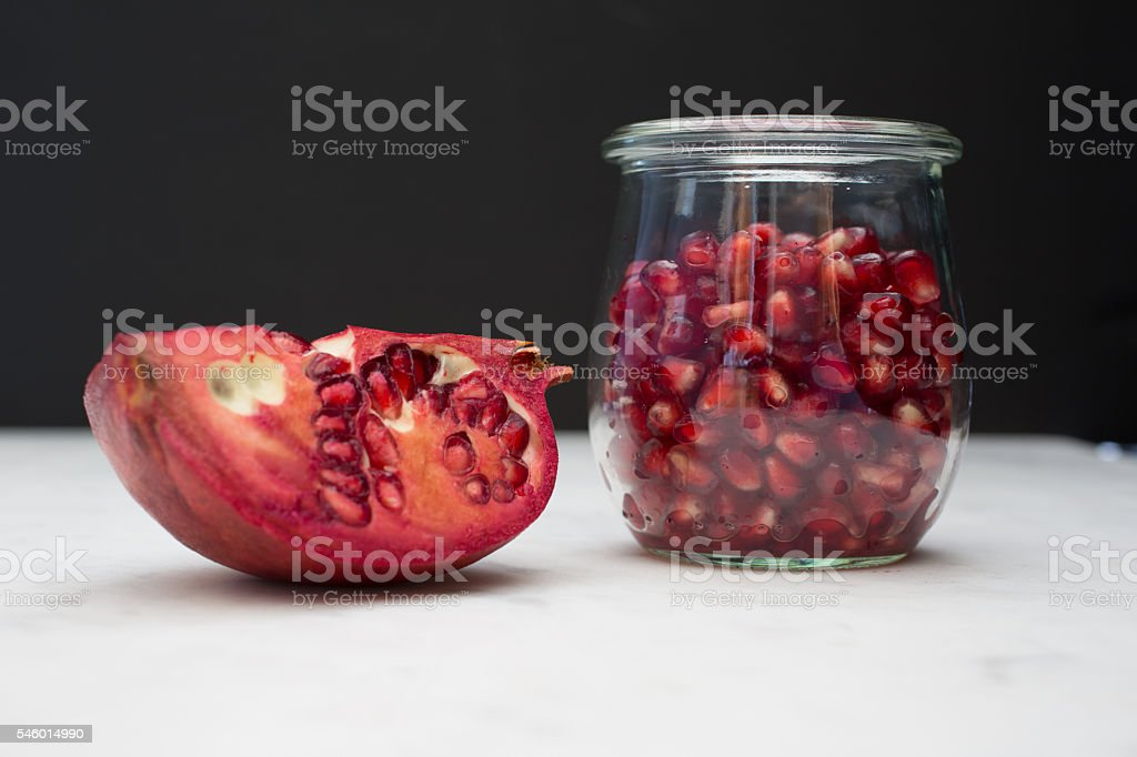 Pomegranate & arils on black and white stock photo