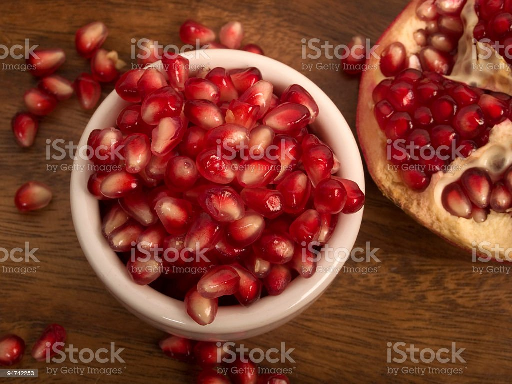 Pomegranate Seeds on Wood stock photo