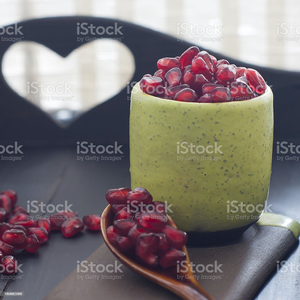 Pomegranate seeds  portion in green pottery stock photo