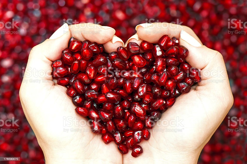 Pomegranate seeds shaping heart in hands stock photo