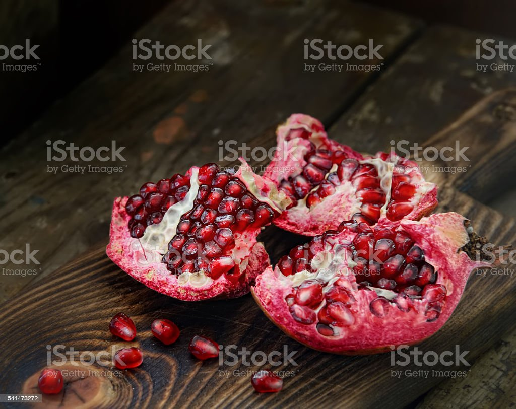 Pomegranate with arils on brown wooden board stock photo