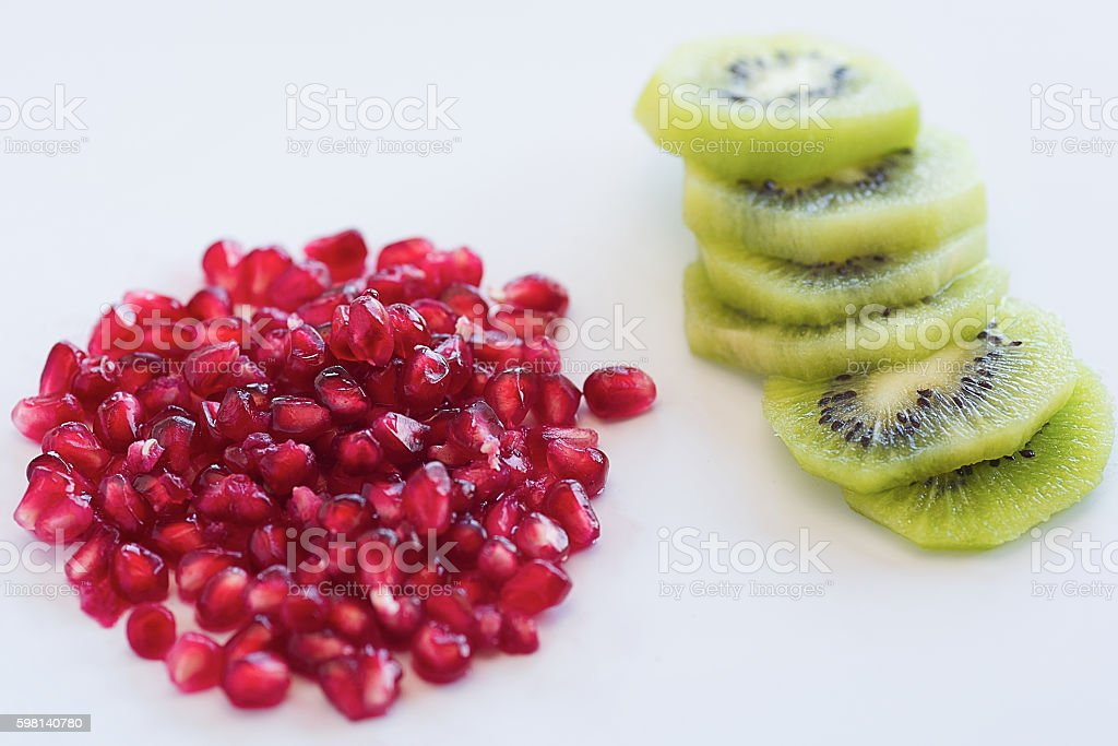 Pomegranate with Kiwi fruit and slices on white background with stock photo