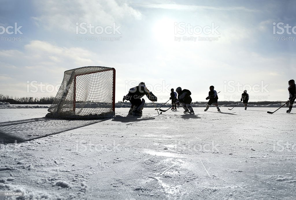 \'A wide shot of a group of kids playing pond hockey on a bright and...