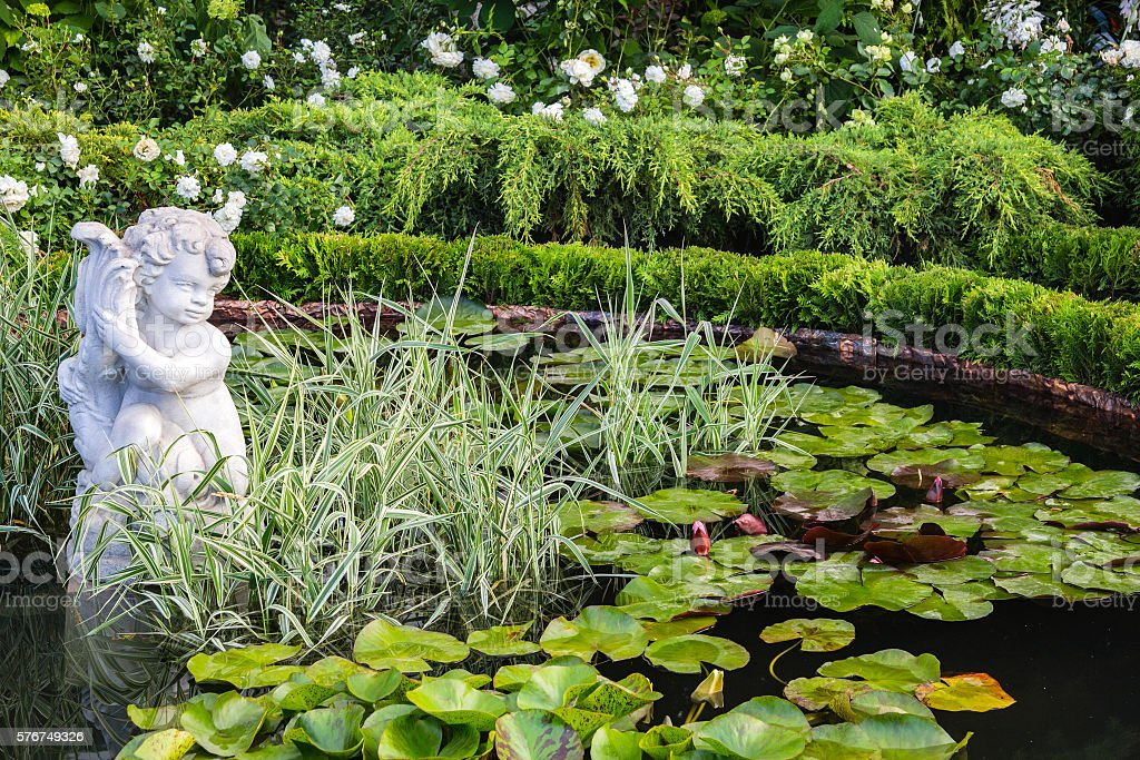pond with water lilies and a statue of an angel stock photo