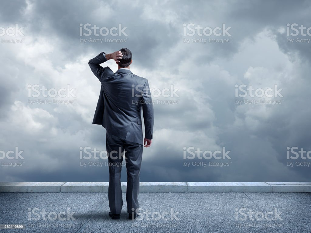 Pondering businessman looking out towards stormy sky stock photo