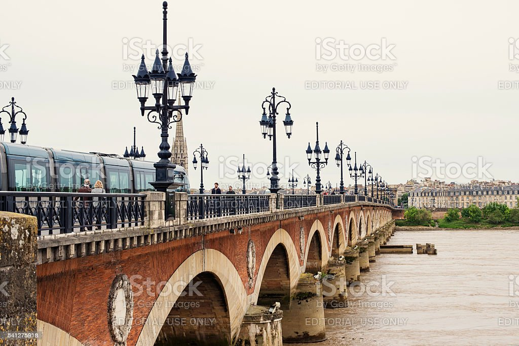 Pont de pierre and tramway with people in Bordeaux, France. stock photo