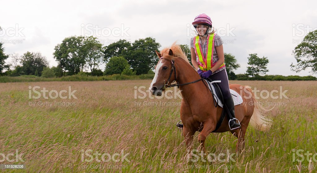 Pony and girl riding in meadow  of long grass royalty-free stock photo