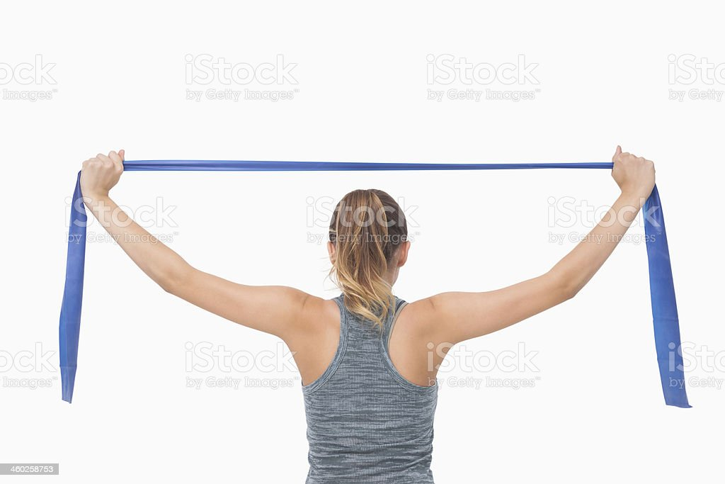 Ponytailed woman training with a resistance band stock photo