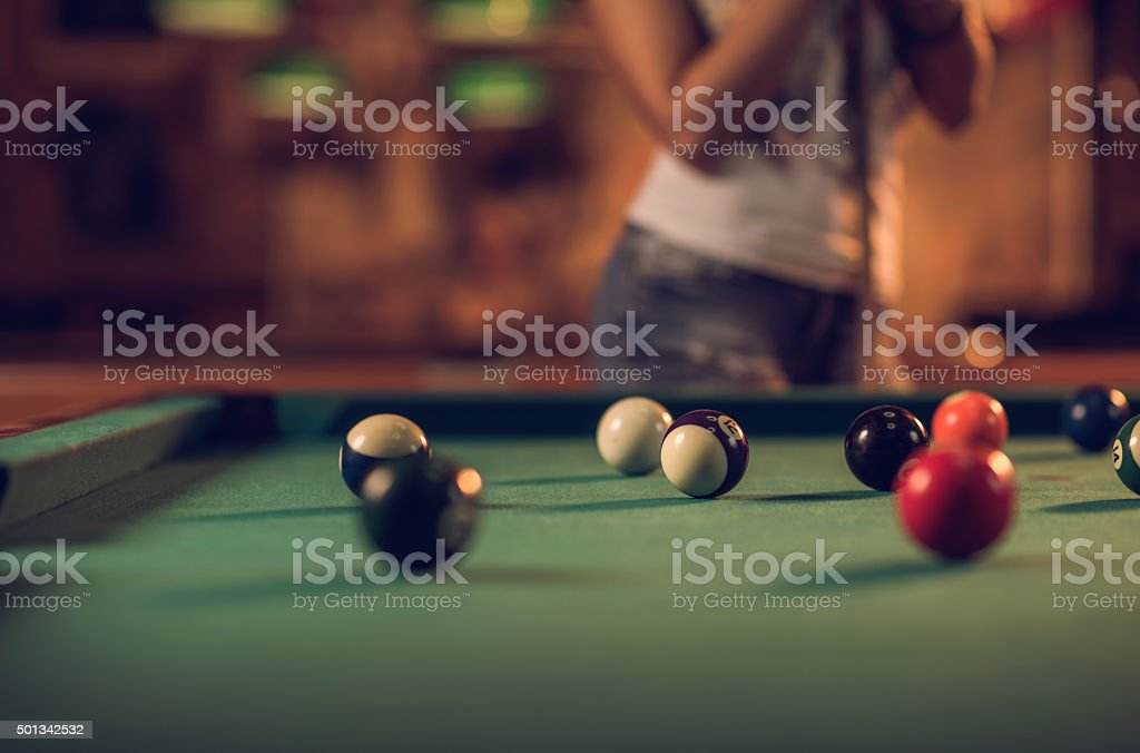 Group of pool balls on a table with a person in the background.