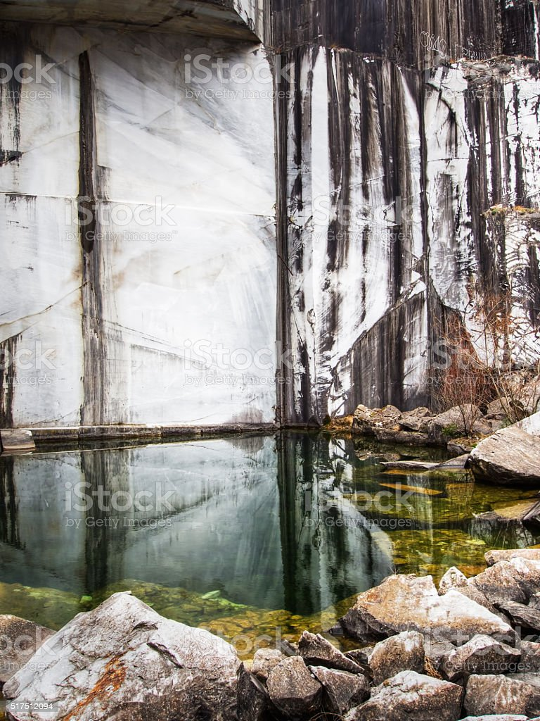 Pool in abandoned old marble quarry. Vertical. stock photo