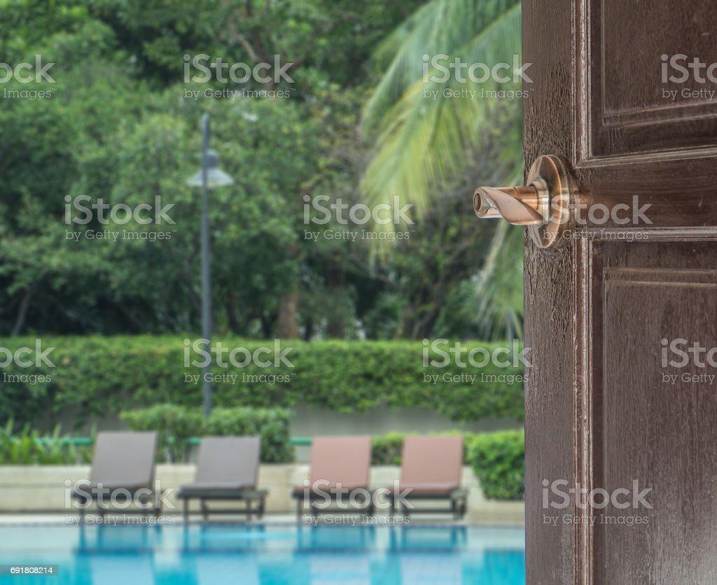opened door to swimming pool in large garden, concept