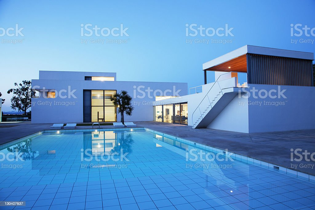 Pool outside modern house at twilight stock photo