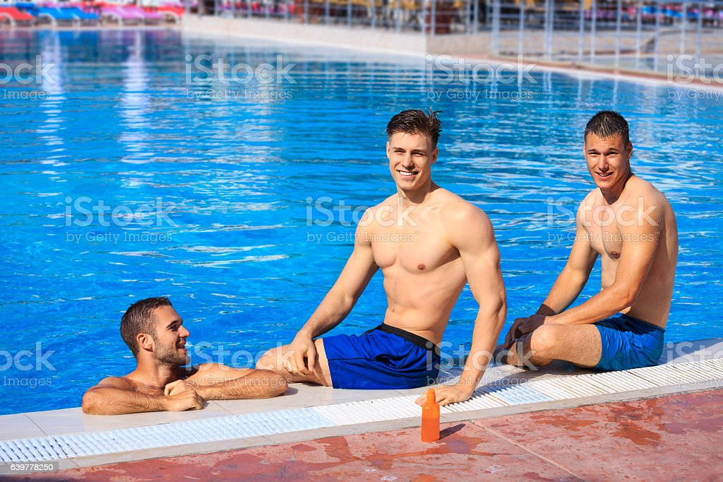 Pool party   Friends  Three young man relaxing at swimming pool stock photo