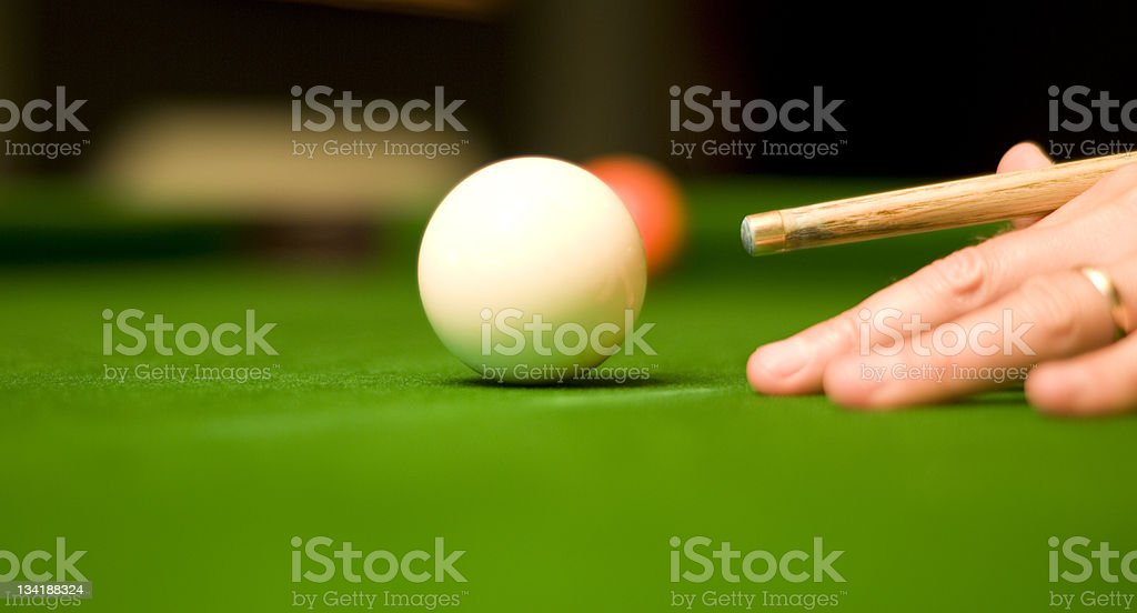 Pool player with cue poised to hit cue ball royalty-free stock photo