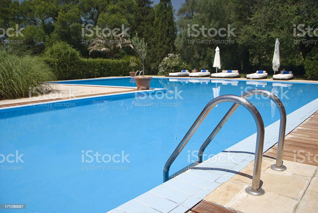 Pool steps leading into a blue swimming pool royalty-free stock photo