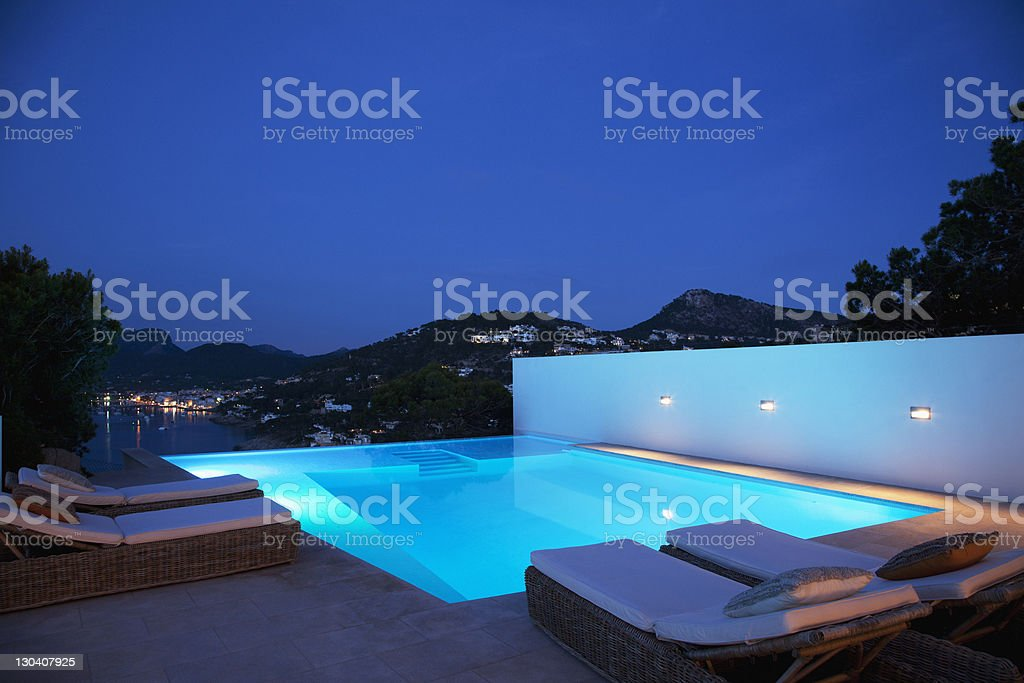 Pool with lounge chairs at night stock photo