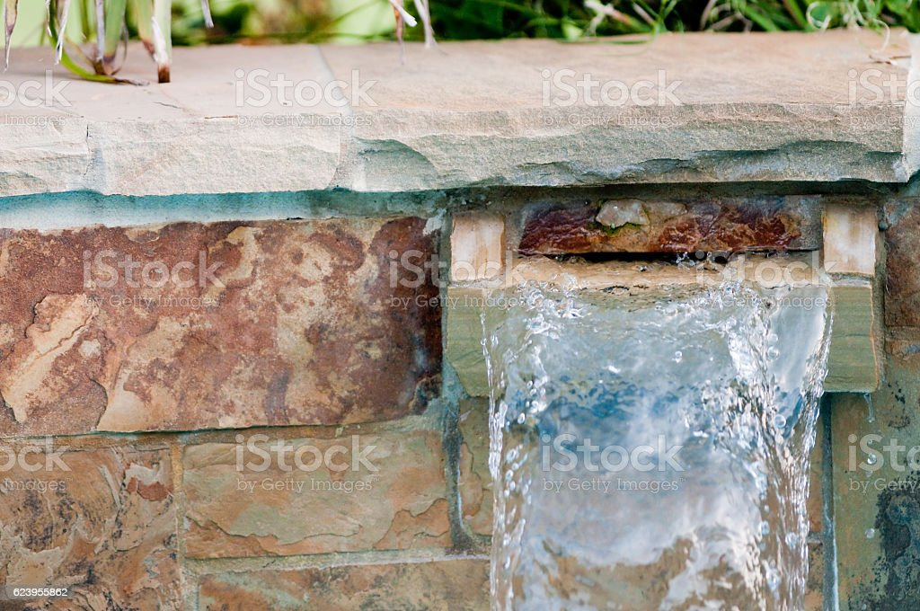 Poolside stone waterfall with copy space stock photo