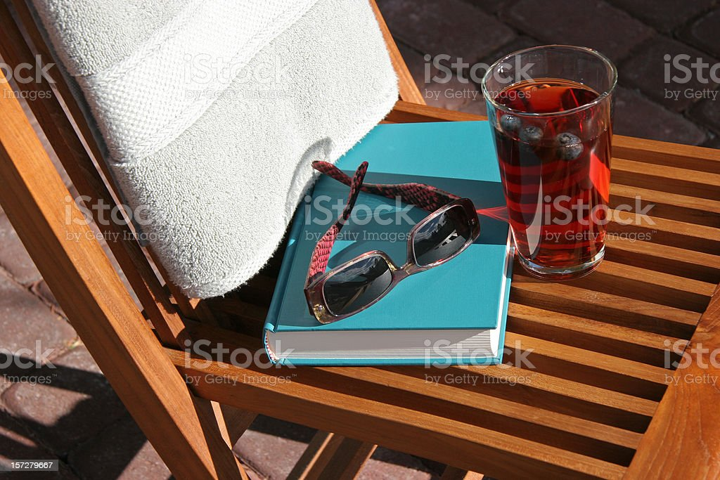 Poolside With Old Fashioned Book, Sunglasses and Drink stock photo