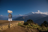 Poon hill altitude sign with Annapurna range in background, Nepal.