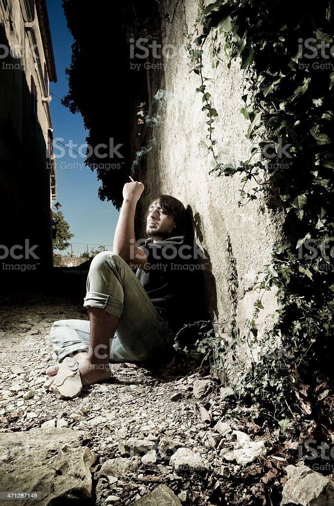 Poor and drugged young man on the narrow streets royalty-free stock photo
