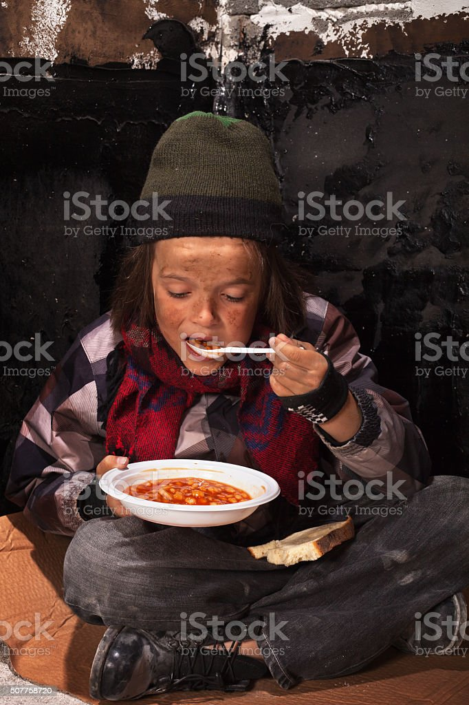 Poor beggar child eating charity food stock photo