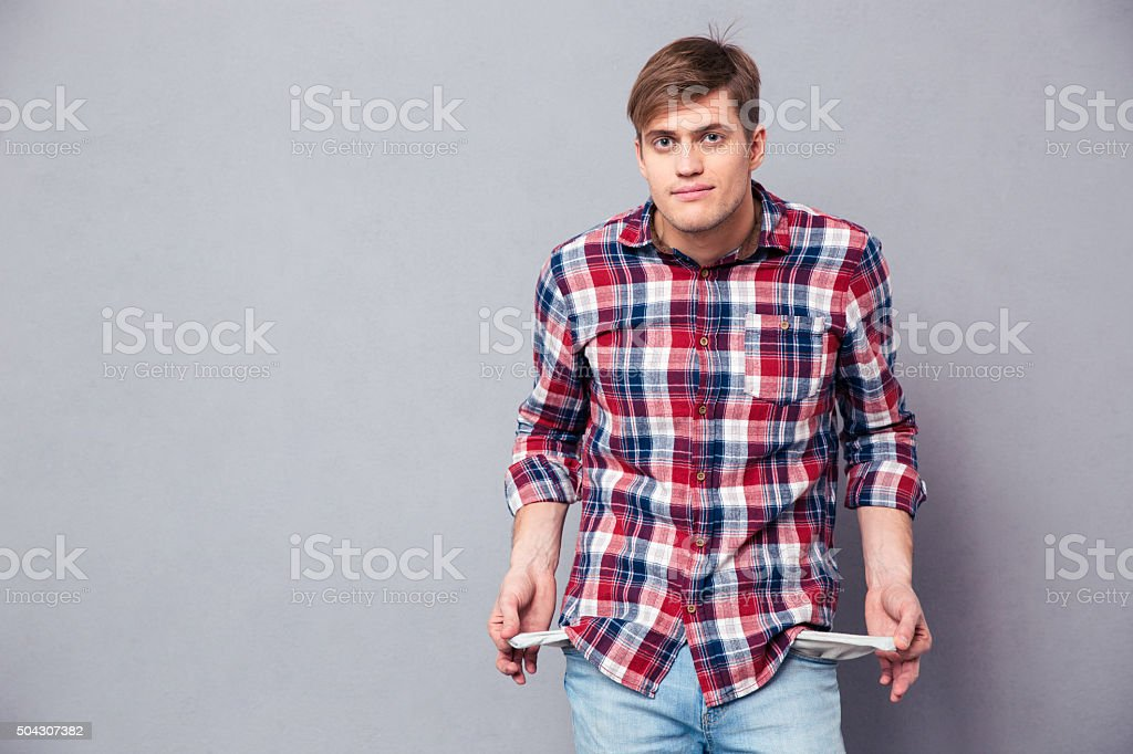 Poor handsome young man in checkered shirt showing empty pockets stock photo